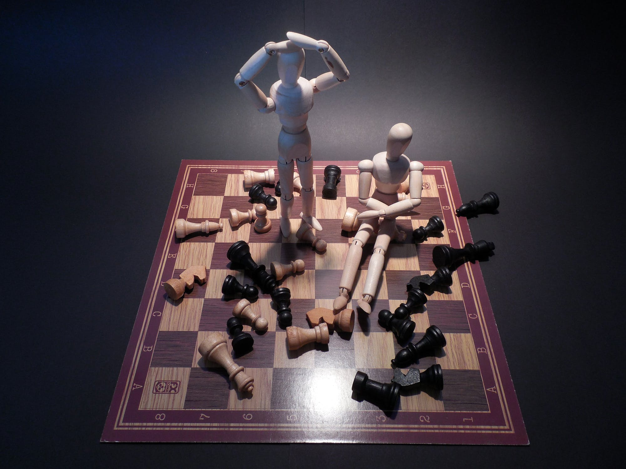 Human figures sharing chess board with chess pieces